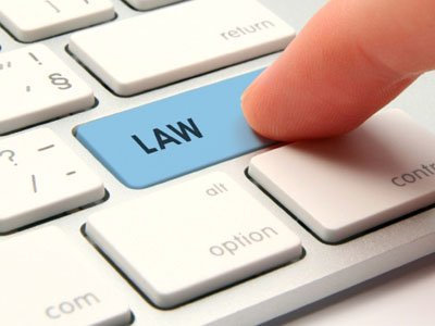 Computer law and justice concept - modernized computer keyboard with law keypad. Computer user searching legal services.