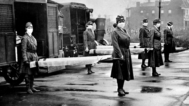During the influenza epidemic, members of the Red Cross Motor Corps, all in uniform with cloth face masks, pose for a portrait with stretchers behind a row of ambulances, St Louis, Missouri, October 1918. (Photo by Library of Congress/Interim Archives/Getty Images)